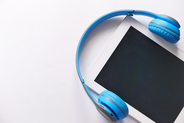 Hörbuchkonzept. kopfhörer und digitales tablet auf dem tisch.