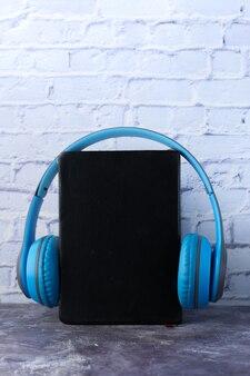 Hörbuchkonzept. kopfhörer und notizblock an weißer wand