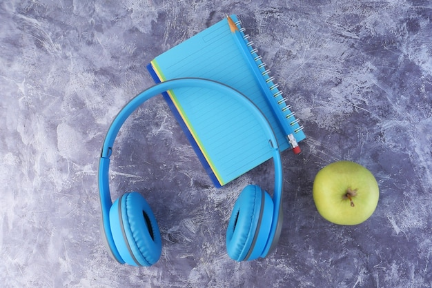 Hörbuchkonzept-kopfhörer und notizblock auf schwarzem hintergrund