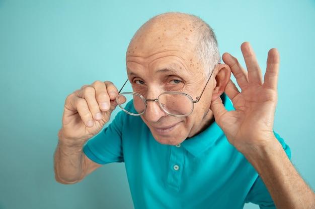 Höre auf geheimnisse. porträt des kaukasischen älteren mannes auf blauem studio.