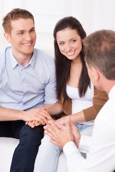 Hören sie auf einen expertenrat. glückliches junges paar, das finanzangelegenheiten mit finanzberater bespricht