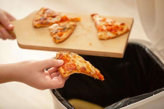 Hören sie auf, essen zu verschwenden, frau hand wirft etwas essen, pizzastücke in den mülleimer, müll, lebensmittelkonzept