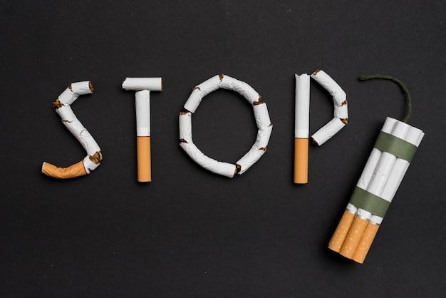 Hören sie auf, konzept mit bündel zigaretten und docht gegen schwarzen hintergrund zu rauchen