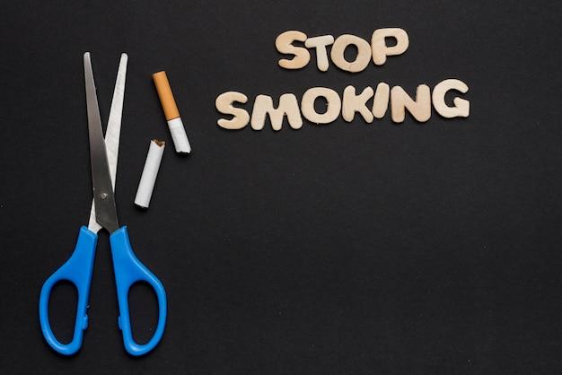 Hören sie auf, text mit schere und defekter zigarette auf schwarzem hintergrund zu rauchen
