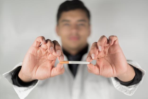 Hören sie auf, zigaretten zu rauchen konzept. porträt des arztes, der gebrochene zigarette in händen hält. mit dem rauchen aufhören. beenden sie schlechte angewohnheit, gesundheitskonzept. rauchen verboten.