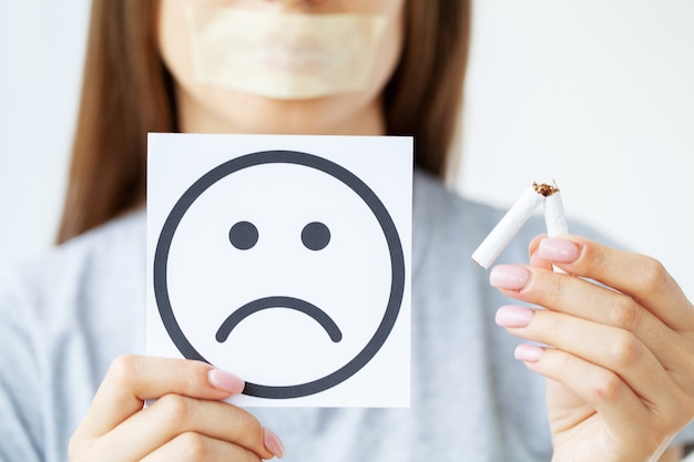 Hören sie auf zu rauchen, frau, die gebrochene zigarette in händen und karte mit traurigem lächeln hält.