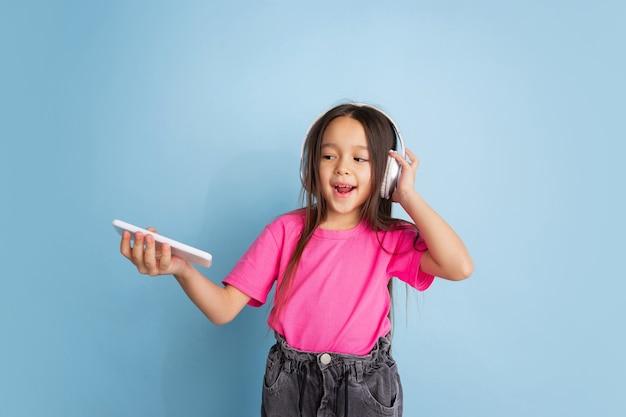 Hören sie das porträt des kaukasischen kleinen mädchens an der blauen wand. schönes weibliches modell im rosa hemd. konzept der menschlichen emotionen, gesichtsausdruck, jugend, kindheit.