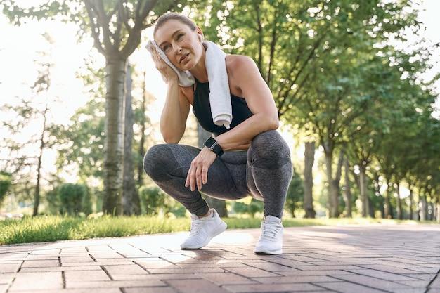 Hören sie nicht auf, müde athletische frau mittleren alters in sportkleidung nach dem laufen ihren schweiß mit einem handtuch abzuwischen