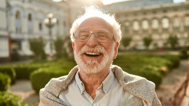Hören sie nicht auf zu lachen, porträt eines glücklichen und gutaussehenden älteren mannes mit brille, der in die kamera schaut und