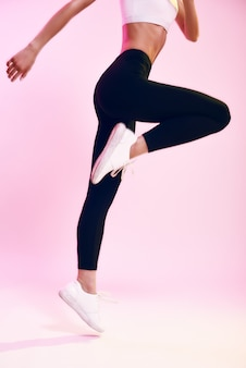 Hören sie nie auf abgeschnittenes foto einer sportlichen jungen frau in schwarzen leggings, die vor rosa hintergrund springt