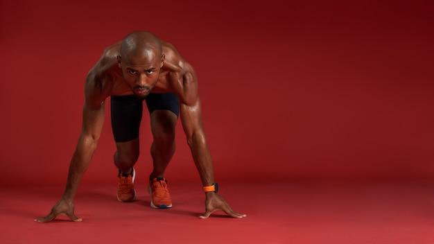 Hören sie nie auf, das porträt eines jungen afrikanischen mannes in sportkleidung zu laufen, während er isoliert sitzt