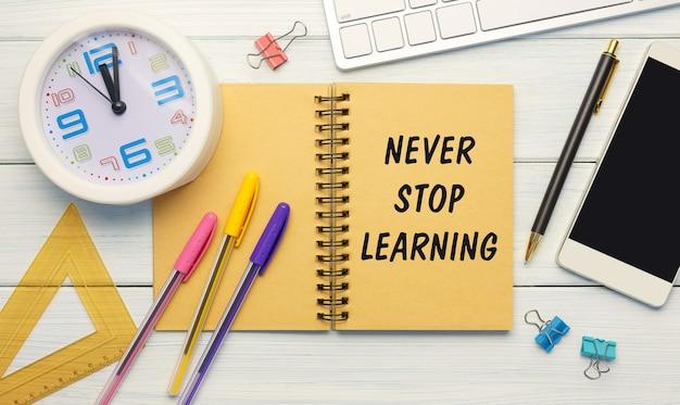 Hören sie nie auf zu lernen, geschrieben auf einem notizbuch mit büromaterial auf weißem holzhintergrund