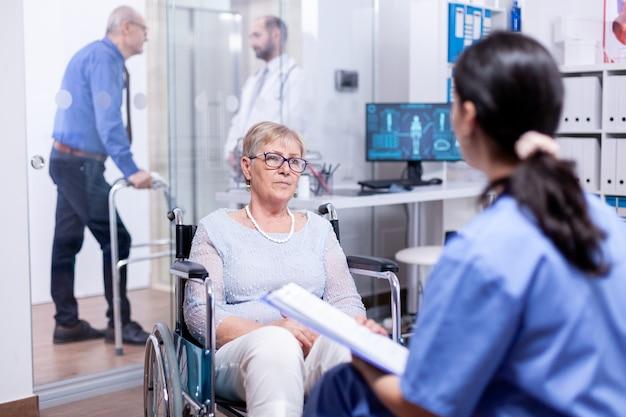 Hörende krankenschwester der behinderten frau, die während der beratung über genesungsbehandlung und krankenversicherung spricht