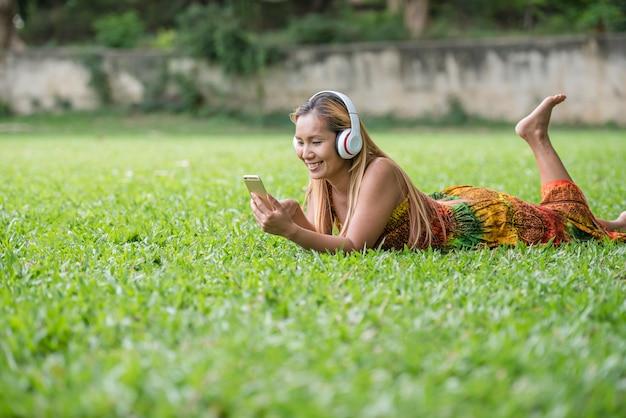 Hörende lieblingsmusik der asiatin auf kopfhörern. glückliche zeit und entspannen.