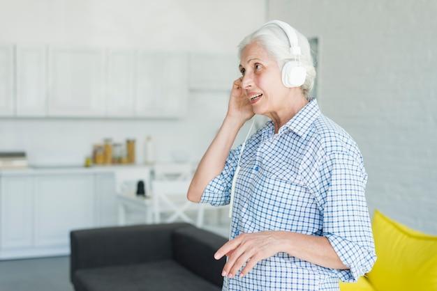 Hörende musik der älteren frau auf kopfhörer zu hause