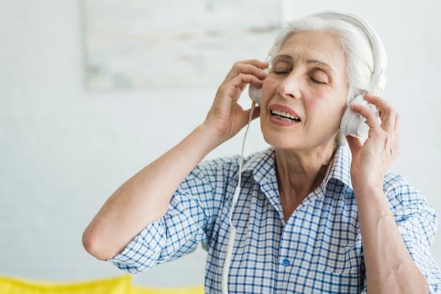 Hörende musik der älteren frau auf kopfhörer