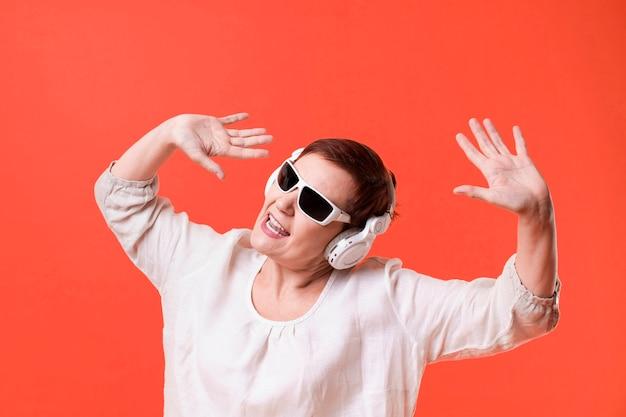 Hörende musik der frau auf rotem hintergrund