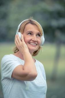 Hörende musik der glücklichen älteren frau auf kopfhörer im park