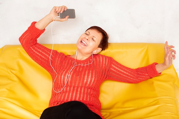 Hörende musik der glücklichen älteren frau