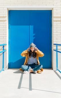 Hörende musik der glücklichen frau am intelligenten telefon, das draußen gegen blaue tür sitzt