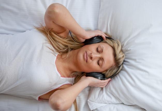 Hörende musik der hellen frau auf einem bett