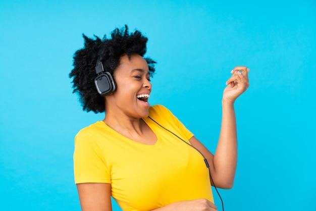 Hörende musik der jungen afroamerikanerfrau mit einem mobile über lokalisierter blauer wand