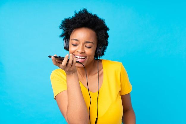 Hörende musik der jungen afroamerikanerfrau mit einem mobile