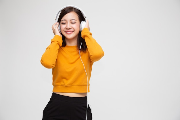 Hörende musik der jungen asiatischen schönheitsfrau mit kopfhörern in der wiedergabelistenliedanwendung auf dem smartphone lokalisiert