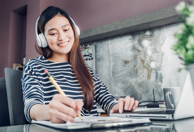 Hörende musik der jungen asiatischen zufälligen geschäftsfrau und schreiben des berichts