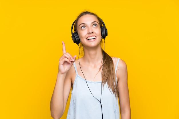 Hörende musik der jungen frau auf der gelben wand, die beabsichtigt, die lösung beim anheben eines fingers zu verwirklichen