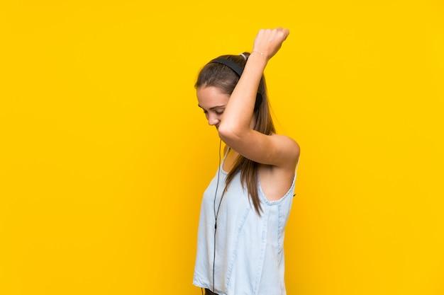 Hörende musik der jungen frau auf gelber wand
