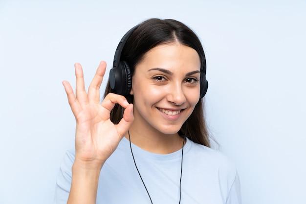 Hörende musik der jungen frau, die okayzeichen mit den fingern zeigt