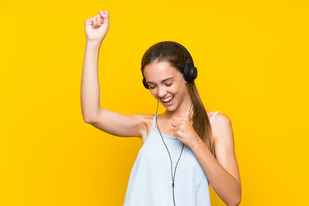 Hörende musik der jungen frau lokalisiert auf der gelben wand, die einen sieg feiert