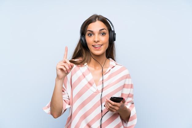Hörende musik der jungen frau mit einem mobile eine großartige idee oben zeigend