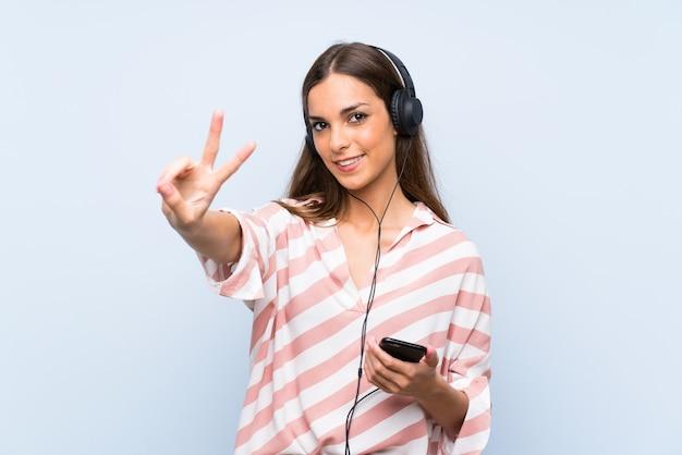 Hörende musik der jungen frau mit einem mobile lächelnd und siegeszeichen zeigend