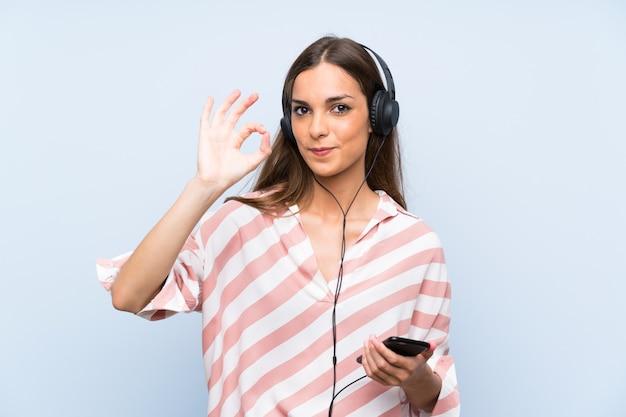 Hörende musik der jungen frau mit einem mobile über der lokalisierten blauen wand, die okayzeichen mit den fingern zeigt