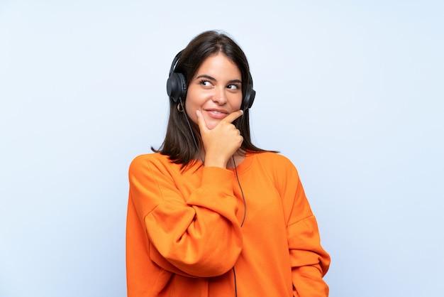 Hörende musik der jungen frau mit einem mobile über lokalisierter blauer wand eine idee denkend