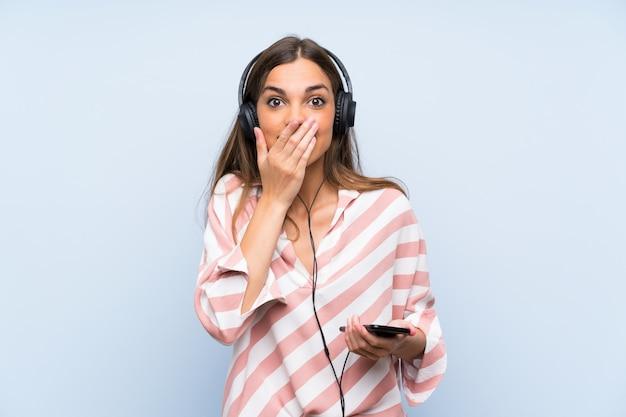 Hörende musik der jungen frau mit einem mobile über lokalisierter blauer wand mit überraschungsgesichtsausdruck
