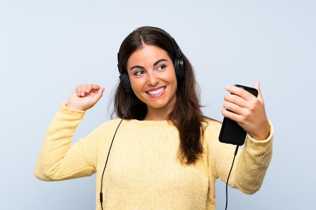 Hörende musik der jungen frau mit einem mobile über lokalisierter blauer wand und tanzen