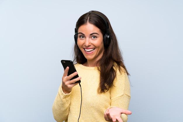 Hörende musik der jungen frau mit einem mobile über lokalisierter blauer wand