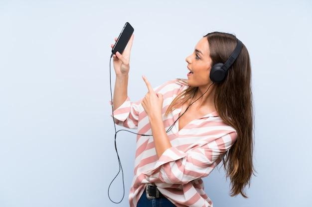Hörende musik der jungen frau mit einer mobile lokalisierten blauen wand