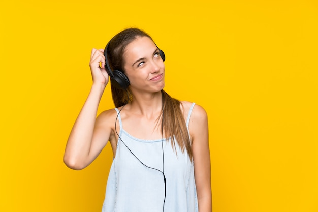 Hörende musik der jungen frau über der lokalisierten gelben wand, die zweifel hat und mit verwirren gesichtsausdruck