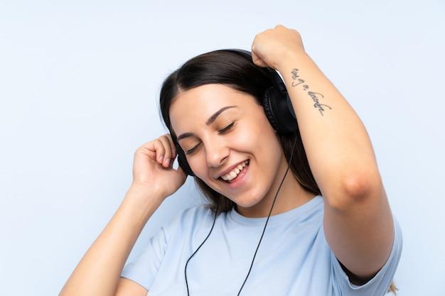 Hörende musik der jungen frau über getrenntem blauem hintergrund