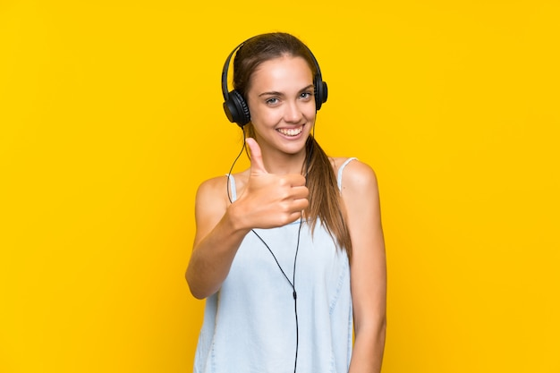 Hörende musik der jungen frau über lokalisierter gelber wand mit den daumen oben, weil etwas gutes geschehen ist
