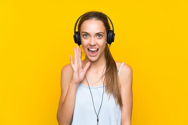 Hörende musik der jungen frau über lokalisierter gelber wand mit überraschung und entsetztem gesichtsausdruck