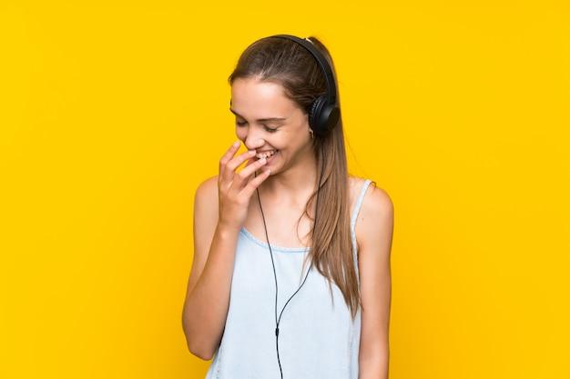 Hörende musik der jungen frau über lokalisierter gelber wand viel lächelnd