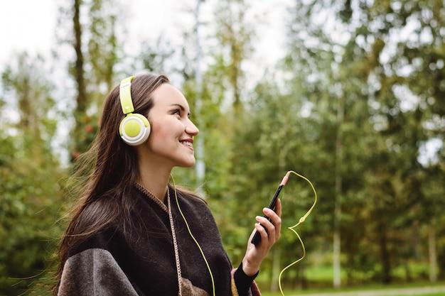 Hörende musik der jungen glücklichen frau vom smartphone mit kopfhörern in einem ruhigen park