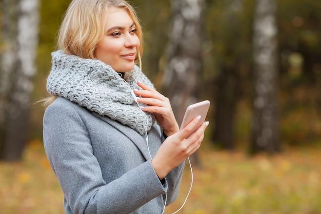 Hörende musik der jungen schönheitsfrau im herbstwald