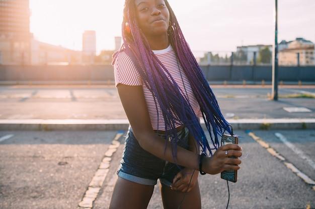 Hörende musik der jungen schwarzen schönheit im freien, die smartphone hält