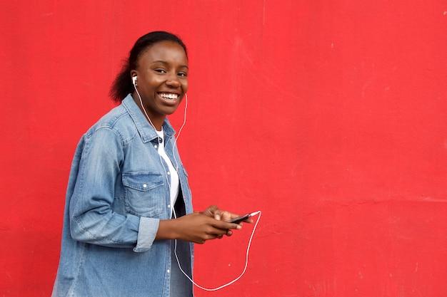 Hörende musik der schönen afrikanischen frau auf mobile